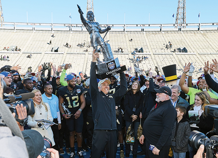 Dave Clawson holding trophy after bowl victory