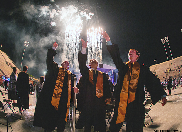 Students celebrate Commencement 2021 as fireworks explode in the background